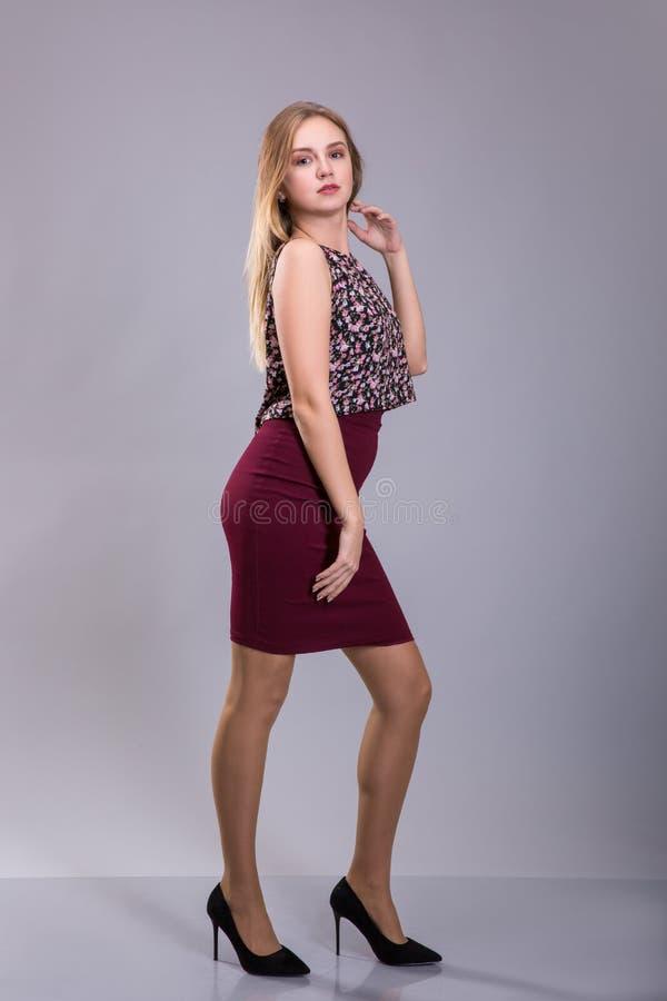 Nätt ung flicka som bär blusen för röd kjol och för blom- tryck Plus format fotografering för bildbyråer