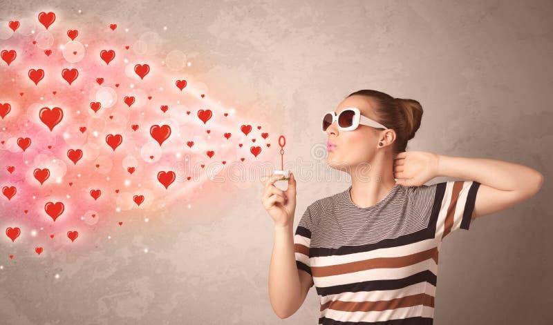 Nätt ung flicka som blåser röda hjärtasymboler royaltyfri bild