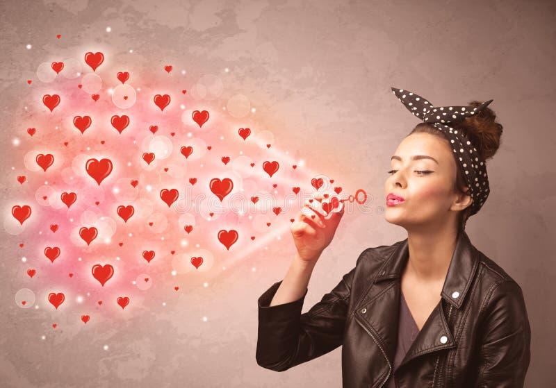 Nätt ung flicka som blåser röda hjärtasymboler royaltyfri foto