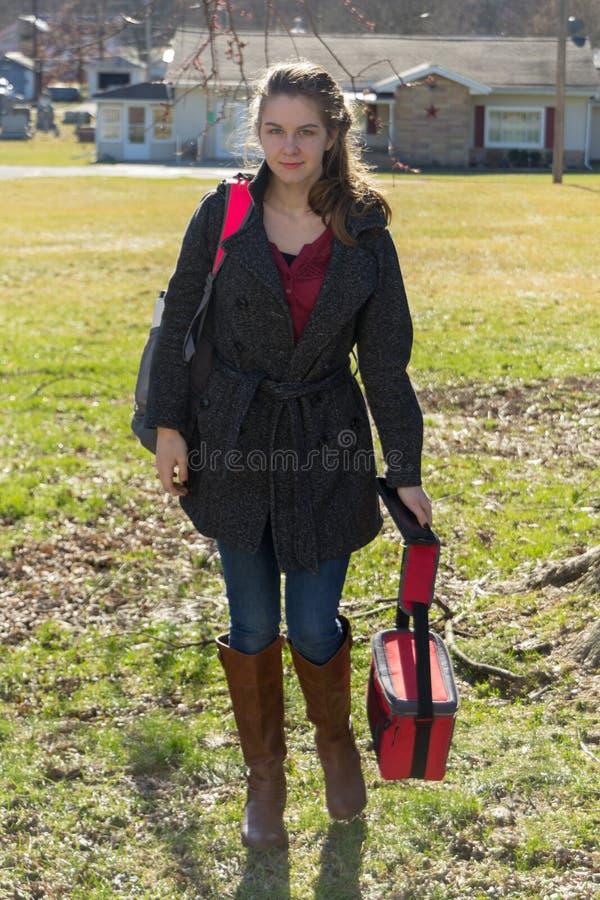 Nätt ung flicka som hem kommer från skola i kängor fotografering för bildbyråer