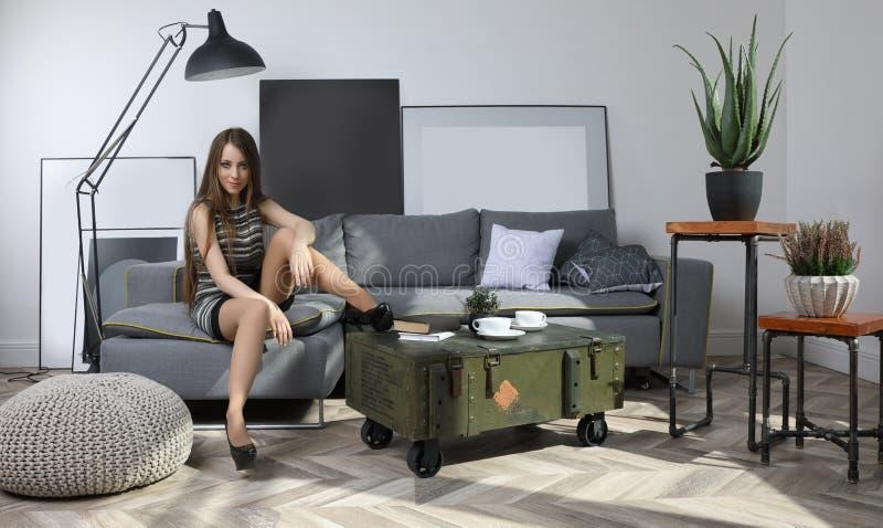 Nätt ung flickasammanträde på soffan i vardagsrum royaltyfri bild