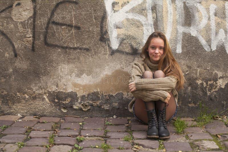 Nätt ung flickasammanträde på trottoaren nära en stenvägg av ett hus staden går arkivbilder