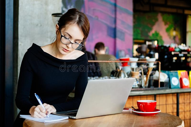 Nätt ung härlig kvinna i exponeringsglas genom att använda bärbara datorn i kafét, slut upp ståenden av affärskvinnan, en dator,  royaltyfri fotografi