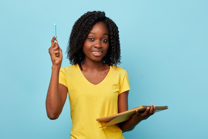 Nätt ung hapy härlig kvinnainnehavlärobok och blå marknadsanteckningsbok royaltyfria bilder