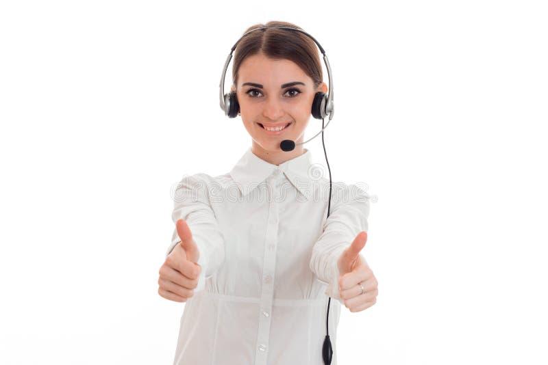 Nätt ung kvinna för arbetare för brunettappellkontor med hörlurar och mikrofonen som ler och visar tummar upp på kamera arkivfoto