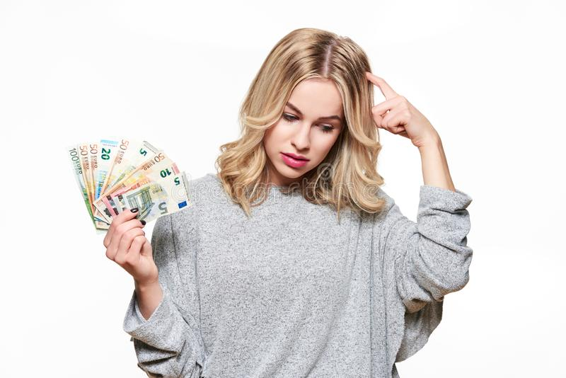 Nätt ung kvinna i den gråa tröjainnehavgruppen av eurosedlar som skrapar hennes head tänka som isolerar på vit fotografering för bildbyråer