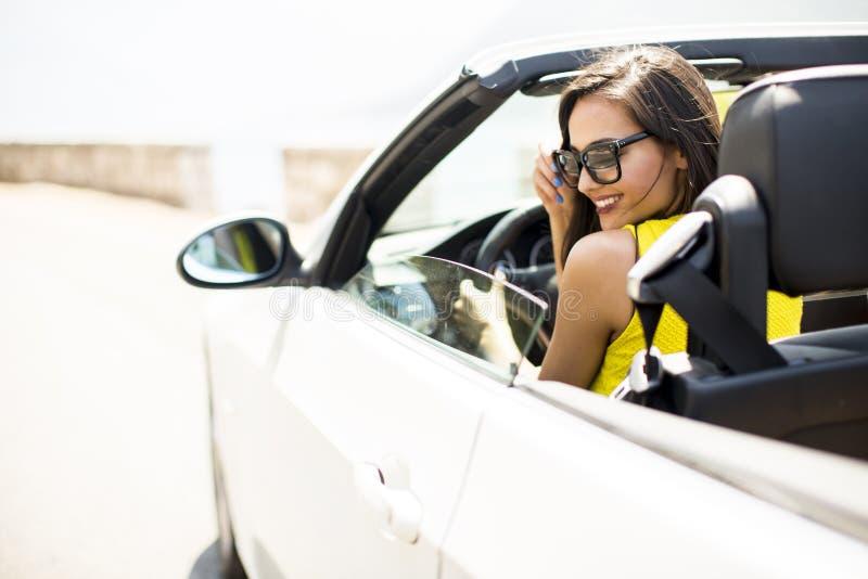 Nätt ung kvinna i den vita cabrioletbilen royaltyfri foto