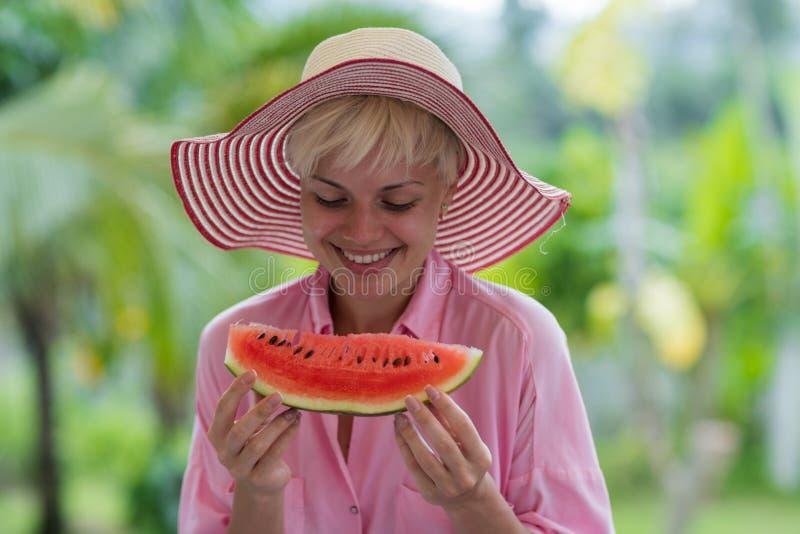 Nätt ung kvinna i hatten som rymmer en skiva av vattenmelon och att le som är lyckliga över tropiska Forest Background arkivfoton