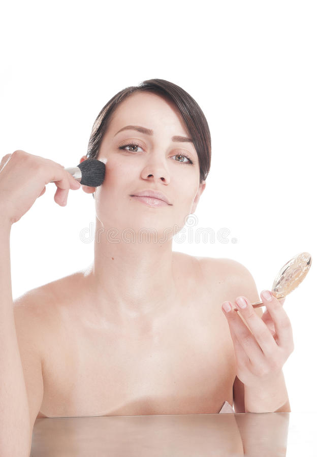 Nätt ung kvinna med en borste som ser i spegeln. Isolerat royaltyfri foto
