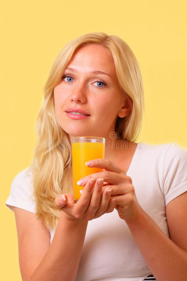 Nätt ung kvinna med ett exponeringsglas av ny fruktsaft royaltyfri foto