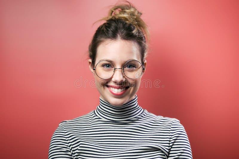 Nätt ung kvinna med glasögon som ser kameran över rosa bakgrund royaltyfri foto