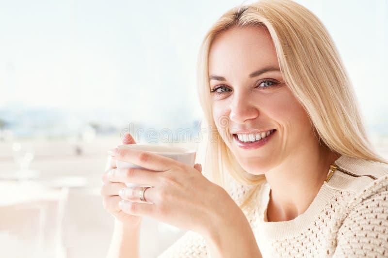 Nätt ung kvinna med koppen kaffe i solig restaurang royaltyfri bild