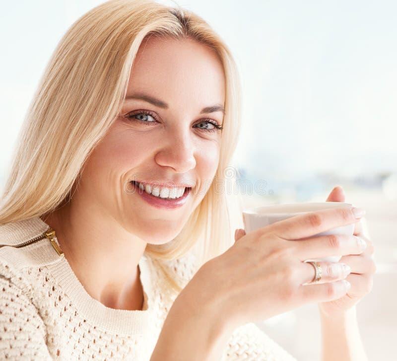 Nätt ung kvinna med koppen kaffe i solig restaurang arkivfoto