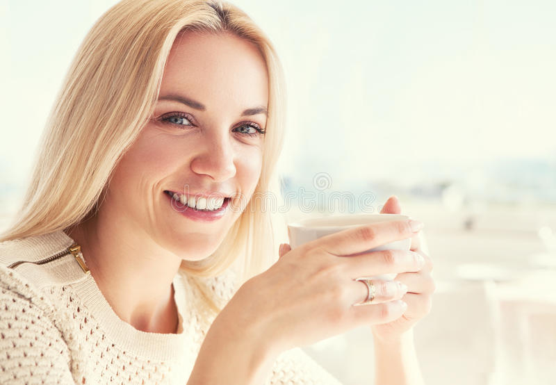 Nätt ung kvinna med koppen kaffe i solig restaurang royaltyfria foton