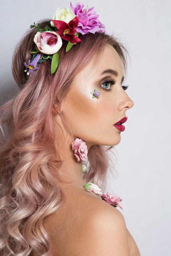 Nätt ung kvinna med kransen av rosa blommor royaltyfri foto