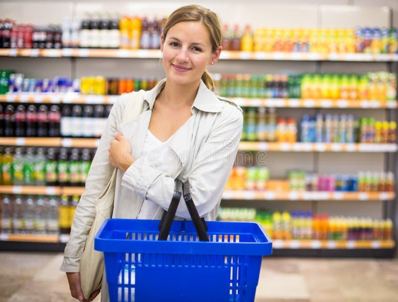 Nätt ung kvinna med livsmedel för en köpande för shoppingkorg royaltyfri fotografi