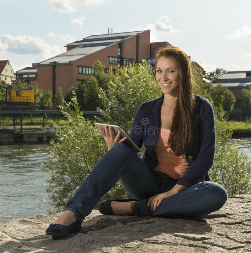 Nätt ung kvinna med minnestavlaPC arkivfoto