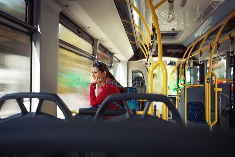 Nätt ung kvinna på en streetcar/autobus, under hennes pendlingssträcka arkivfoto