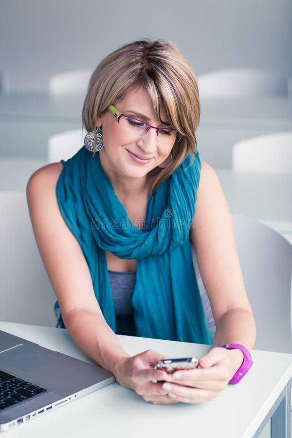 Nätt ung kvinna på ett kontor, genom att använda en bärbar dator arkivbilder