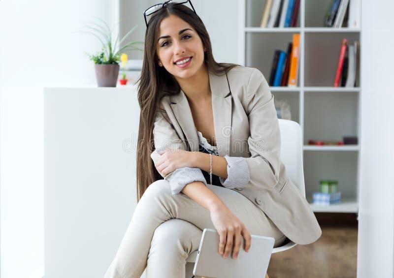 Nätt ung kvinna som använder den digitala minnestavlan i kontoret fotografering för bildbyråer
