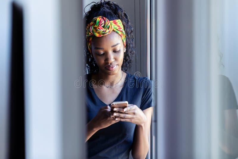 Nätt ung kvinna som använder hennes mobiltelefon, medan stå bredvid fönstret hemma arkivbild