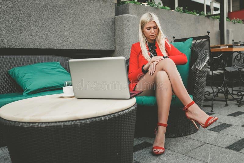 Nätt ung kvinna som arbetar på bärbara datorn och kontrollerar tid på hennes klocka royaltyfri foto
