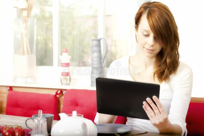 Nätt ung kvinna som bläddrar hennes minnestavla-PC royaltyfri foto