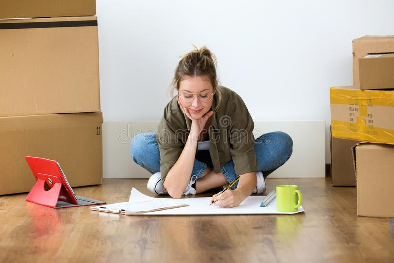 Nätt ung kvinna som drar ritningar av hennes nya hus, medan sitta på golvet hemma arkivbild