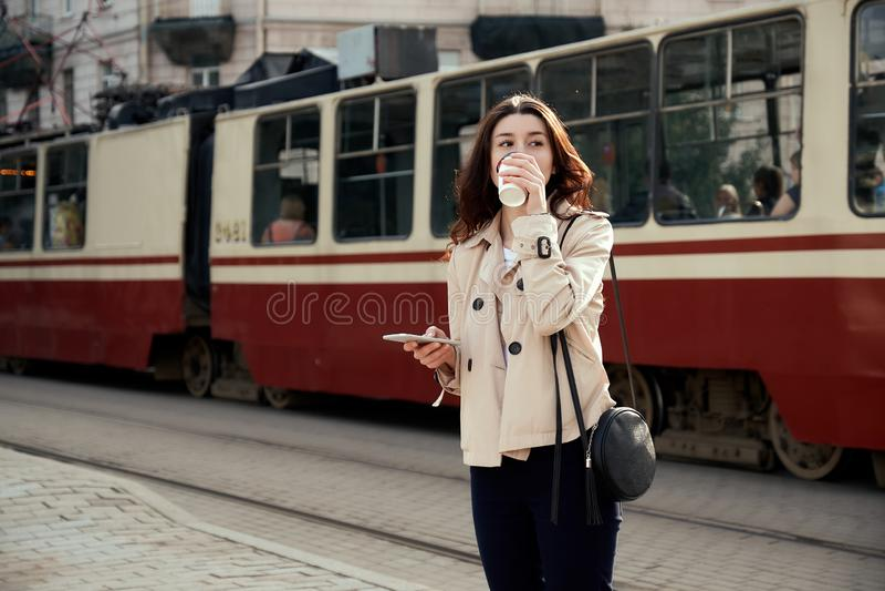 Nätt ung kvinna som dricker den för avhämtning kaffekoppen, genom att använda den smarta telefonen, medan vänta drevet som ankoms fotografering för bildbyråer