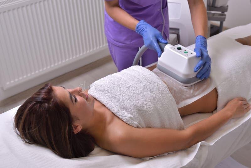 Nätt ung kvinna som får cryolipolysebehandling i professiona arkivfoto