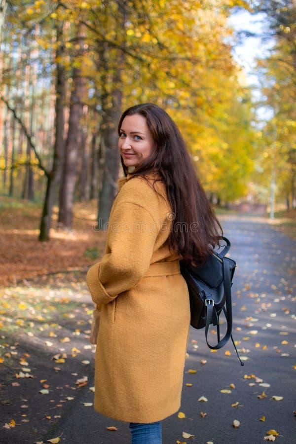 Nätt ung kvinna som går i modern guld- guling för Autumn Park Leaves Fall Relax fritidmode arkivfoto