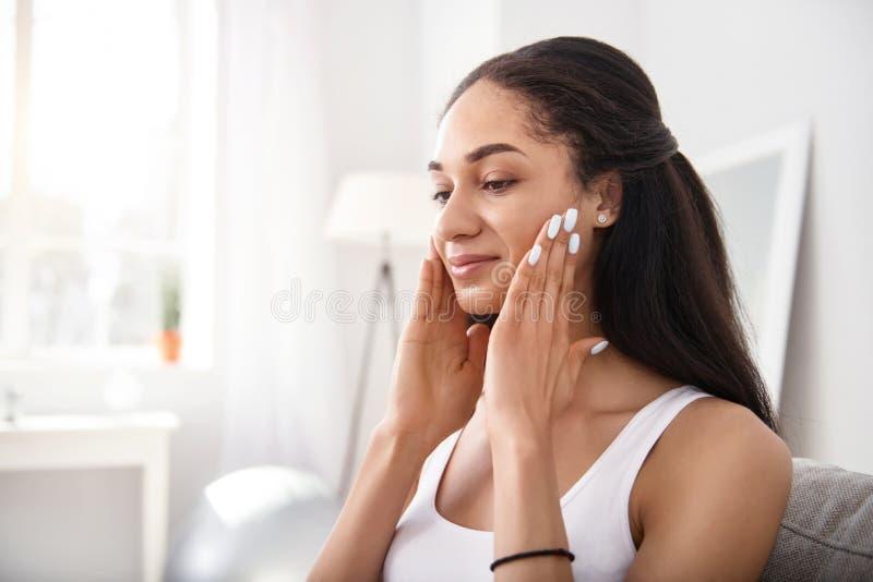 Nätt ung kvinna som gör ansikts- massage fotografering för bildbyråer