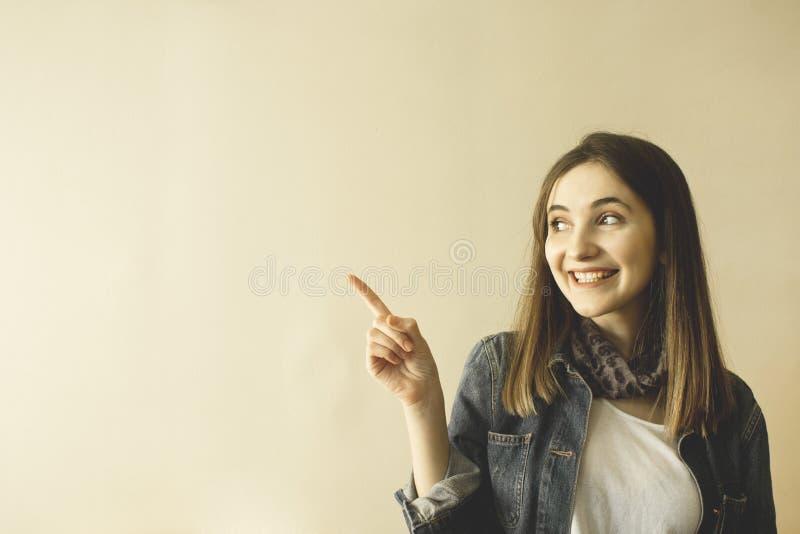 Nätt ung kvinna som gör en gest med fingrar och visar kopieringsutrymme royaltyfri foto