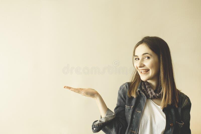 Nätt ung kvinna som gör en gest med handen och visar kopieringsutrymme royaltyfria bilder