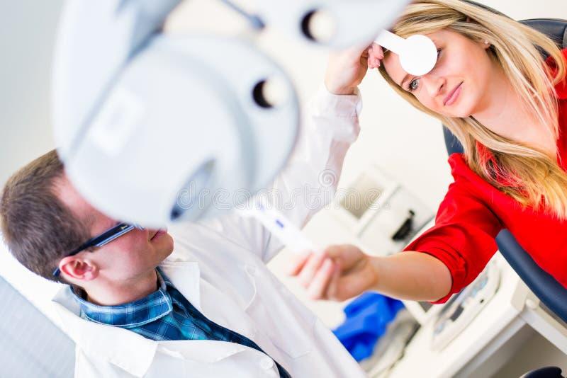 Nätt ung kvinna som har henne undersökta ögon arkivfoton