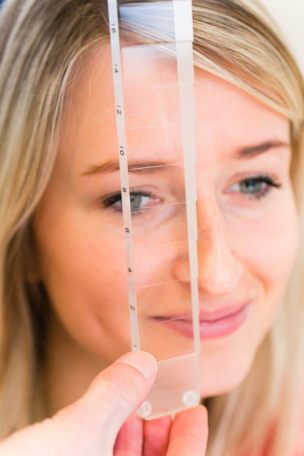 Nätt ung kvinna som har henne undersökta ögon arkivbild