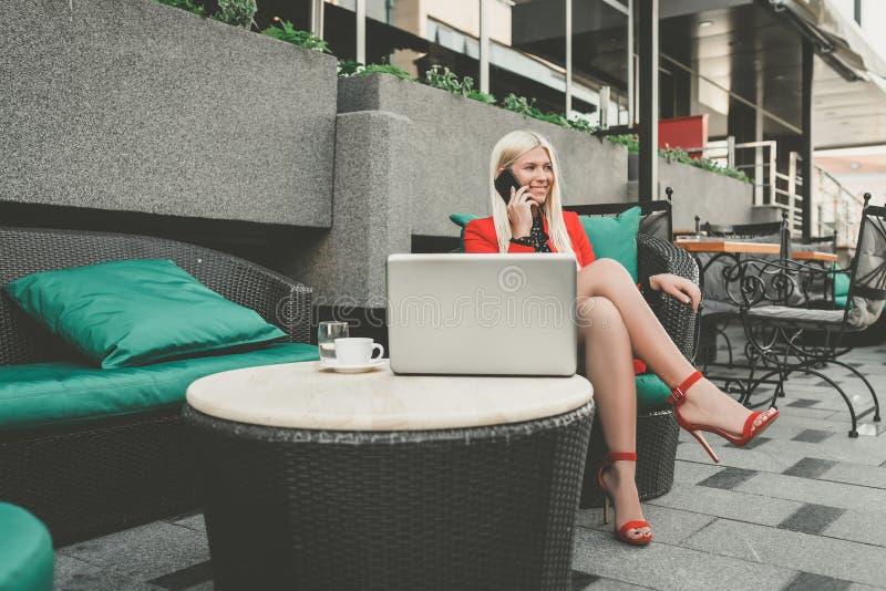 Nätt ung kvinna som har mobiltelefonkonversation, medan sitta den främre öppna bärbar datordatoren fotografering för bildbyråer