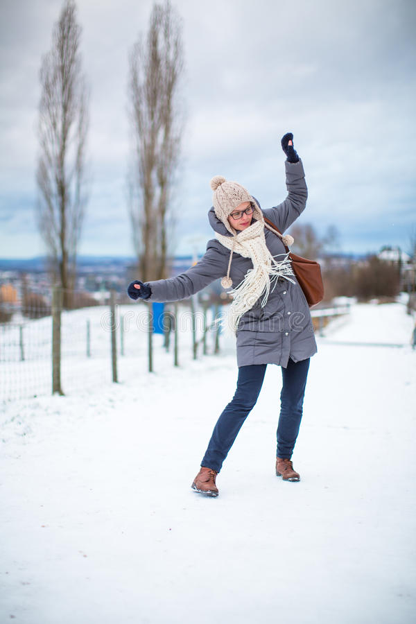 Nätt ung kvinna som har problem som går på ett iskallt arkivfoton