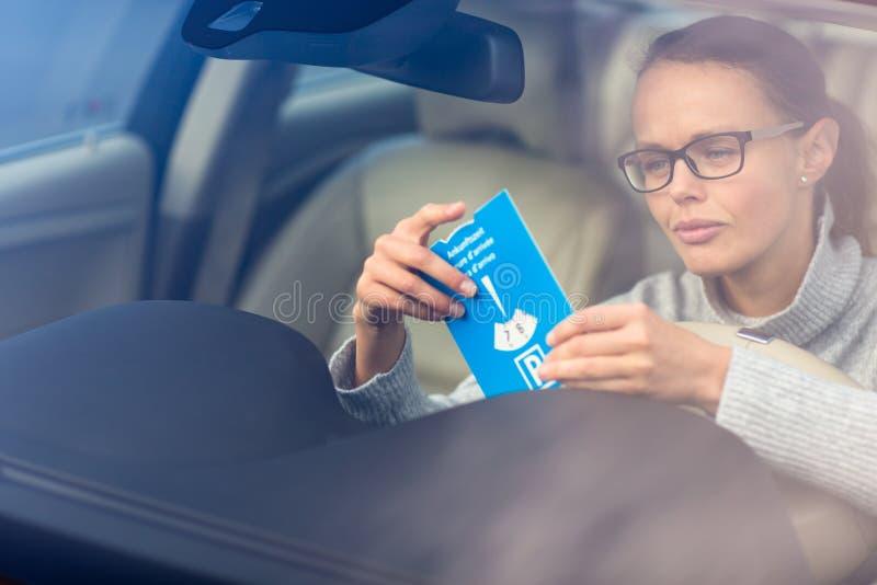 Nätt ung kvinna som kör hennes nya bil- sätta den nödvändiga parkera klockan bak vindrutan royaltyfri fotografi
