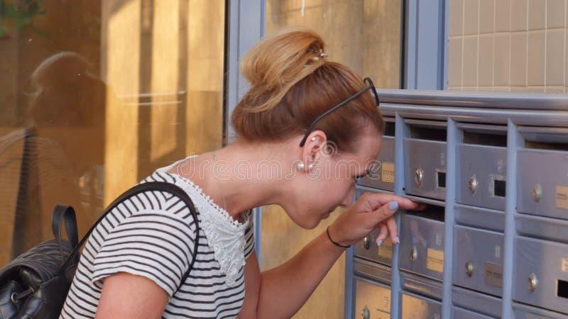 Nätt ung kvinna som kontrollerar hennes brevlåda för nya bokstäver arkivfoton