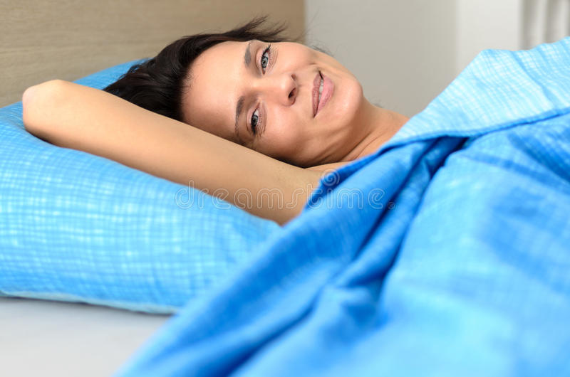 Nätt ung kvinna som kopplar av i säng royaltyfria foton