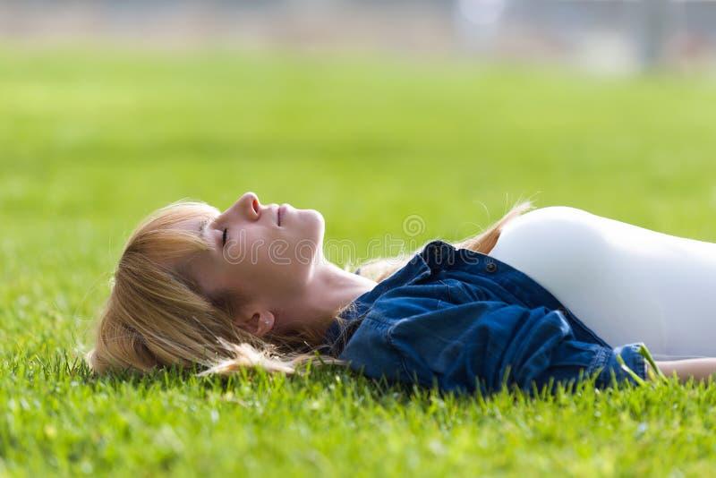 Nätt ung kvinna som kopplar av, medan ligga på gräset i parkera royaltyfri fotografi