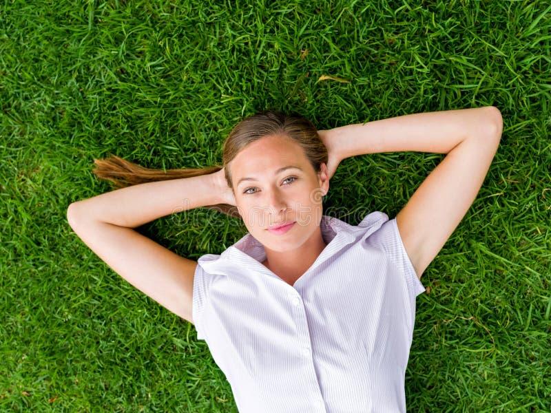 Nätt ung kvinna som kopplar av på ett gräs arkivfoto