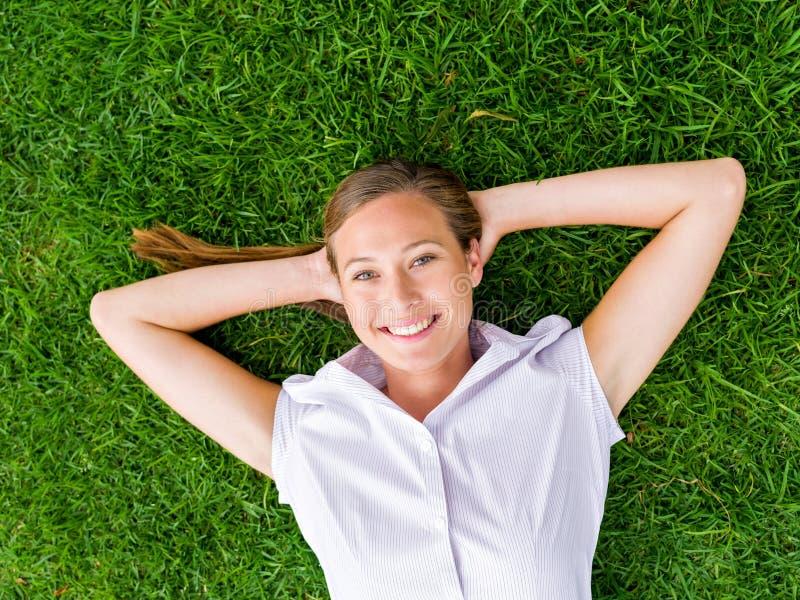 Nätt ung kvinna som kopplar av på ett gräs arkivbilder