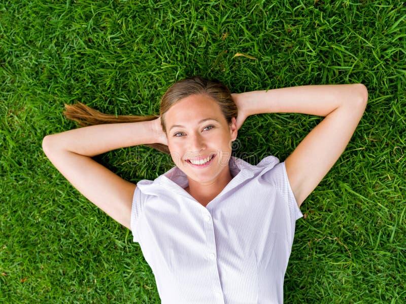 Nätt ung kvinna som kopplar av på ett gräs royaltyfria bilder