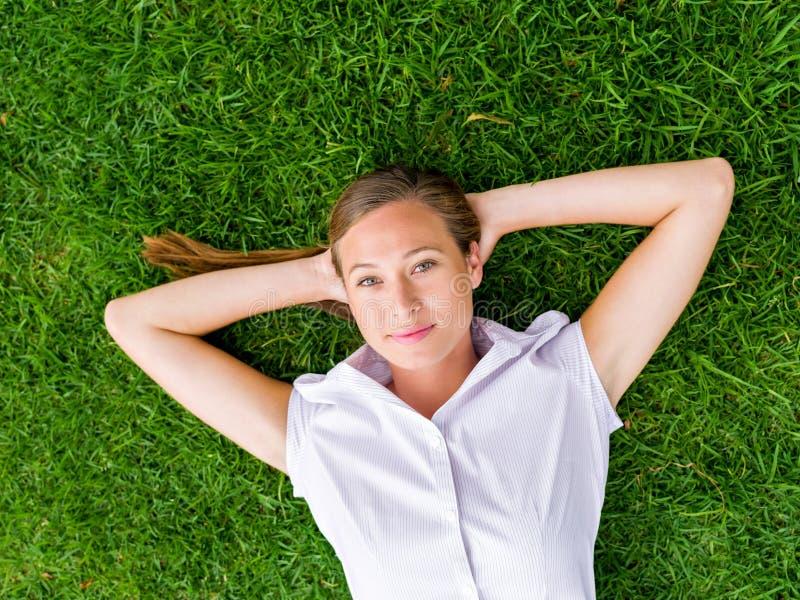 Nätt ung kvinna som kopplar av på ett gräs royaltyfri fotografi