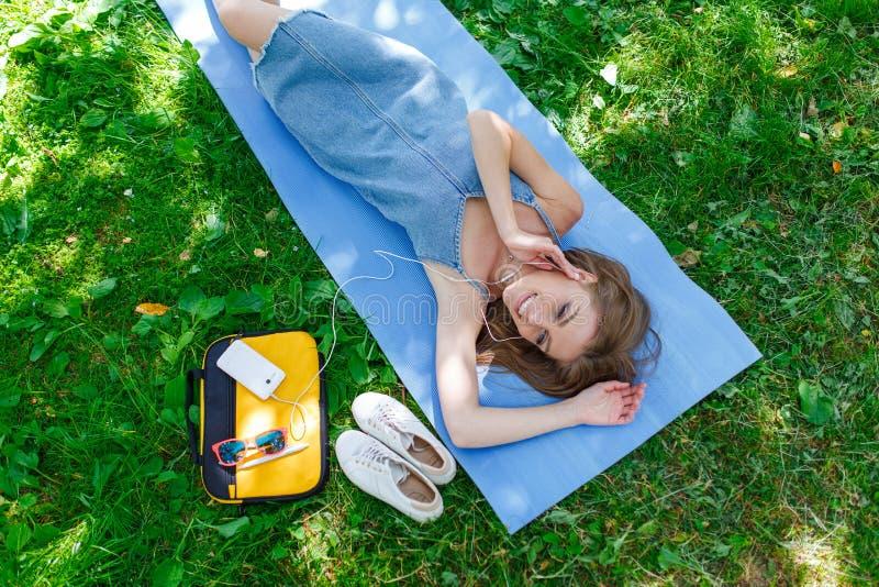 Nätt ung kvinna som kopplar av på gräset i en parkera som lyssnar till musik på hennes mobiltelefon Top beskådar arkivfoton