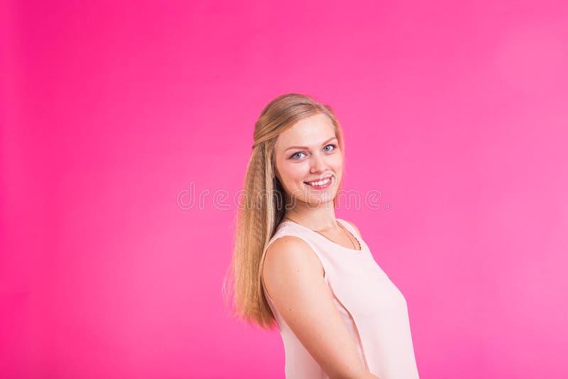 Nätt ung kvinna som ler mot en rosa bakgrund royaltyfria bilder