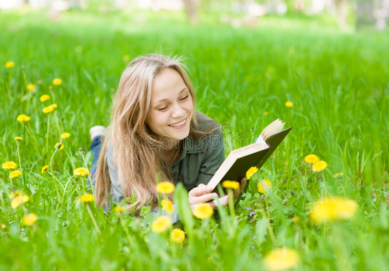 Nätt ung kvinna som ligger på gräs med maskrosor som läser en bok royaltyfri foto