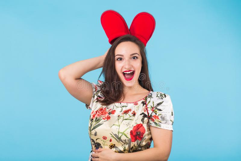 Nätt ung kvinna som omkring bedrar med röda häftklammermatare på blå bakgrund royaltyfria bilder